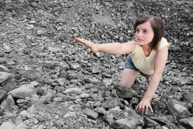 Young woman needs help and stretches her hand from rocky hole